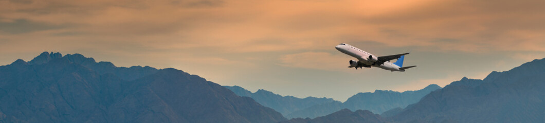 Fototapeta Panoramic view with airplane taken off above mountains,  Middle East