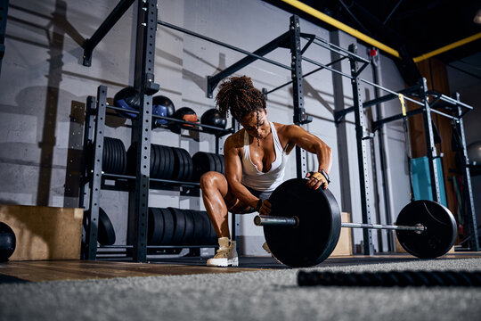 Female weightlifter loading the barbell before the training session