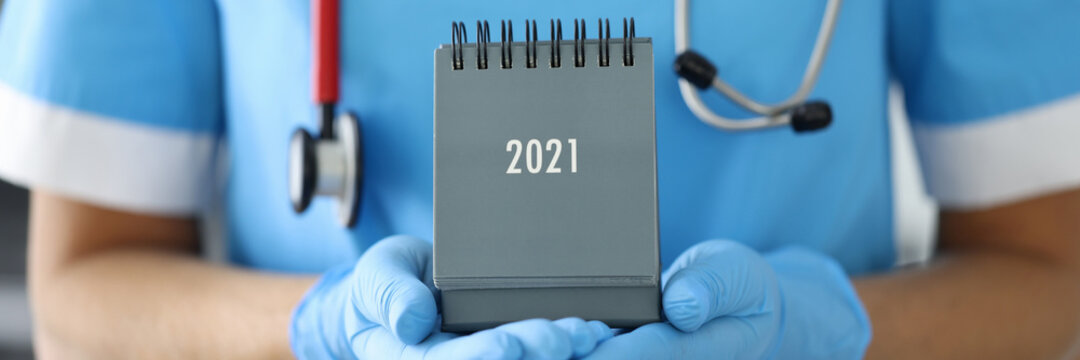 Doctor with phonendoscope around his neck holds desk calendar close-up in rubber gloves. Planning work of medical workers for 2021 concept.