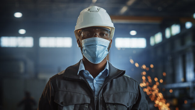 Professional Heavy Industry Engineer/Worker Wearing Safety Face Mask, Uniform, Glasses and Hard Hat in a Steel Factory. African American Industrial Specialist Standing in Metal Construction Facility.