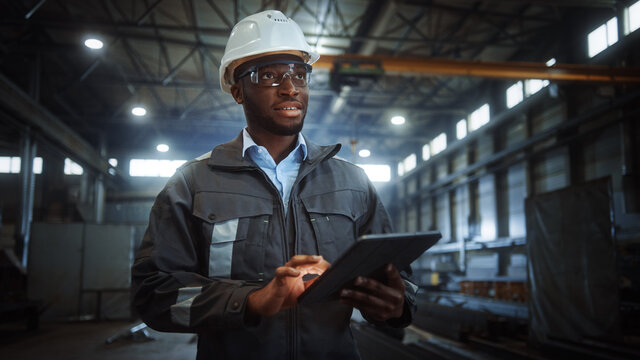 Professional Heavy Industry Engineer/Worker Wearing Safety Uniform and Hard Hat Uses Tablet Computer. Smiling African American Industrial Specialist Walking in a Metal Construction Manufacture.