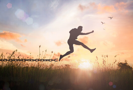 Individual human right day concept: Silhouette of a man jumping and broken chains at orange meadow autumn sunset