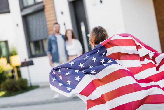 Back view of daughter holding american flag with blurred parents on background