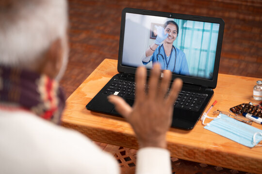Shoulder shot of Old man on video with to doctor on laptop screen - concept of Online Chat, telehealth, or tele counseling with Nurse or Doctor during coronavirus or covid-19 pandemic