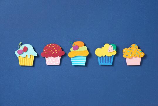 Set cupcake paper cut on blue background