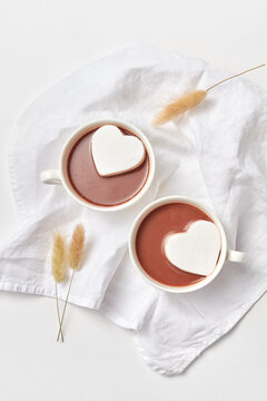 Two cups with chocolate and heart cookies.