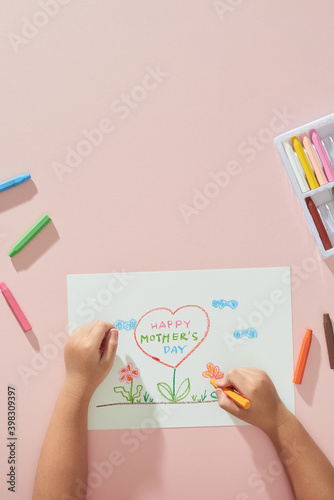 Little boy drawing happy mother's day greeting card on the table. Mother's day background