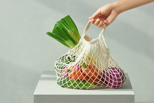 Zero waste eco mesh shopping bag with fruits vegetables grains on chair