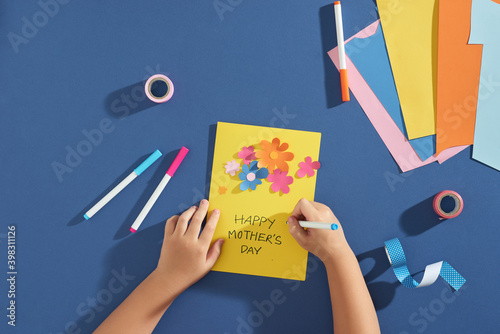 Boy writing on greeting card. Colored paper, decorative elements and tools on child's working desk. School project devoted to Mother's day.