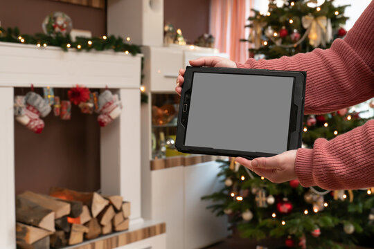 Woman hands holds a PC tablet. The man is standing in a Christmassy decorated living room. Christmas tree and fireplace console.