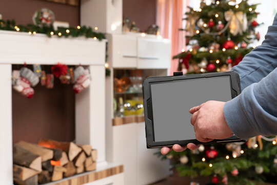 A male hand holds a PC tablet. The man is standing in a Christmassy decorated living room. Christmas tree and fireplace console.