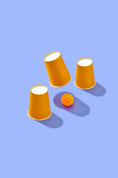 Shell game with paper cups and ball.