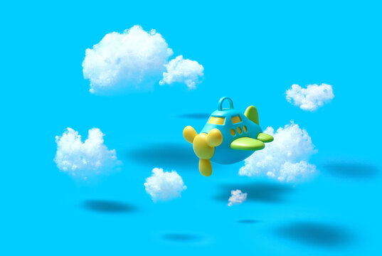 Flying airplain toy in a blue sky with cotton clouds.