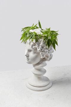 Plaster amur statue with cannabis wreath.