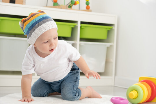 baby toddler boy in funny hat playing with pyramid at home. Developing games for children.