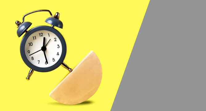 Soaring alarm clock staying with one part on the geometric figure.Concept of the balance in different parts of life.Contemporary style.Banner from yellow and grey parts.
