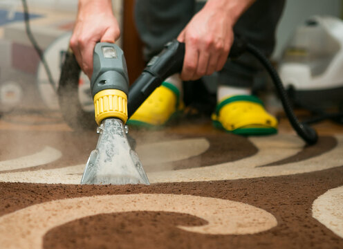 The process of cleaning carpets with a steam vacuum cleaner. An employee of a cleaning company cleans the carpet using steam.
