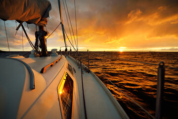 White yacht sailing in an open sea at sunset. A view from the deck to the bow, mast, sails. Epic cloudscape. Dramatic sky with glowing golden clouds after the storm. Racing, sport, leisure activity