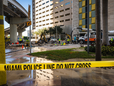 Water main pipe burst and landslide being repaired by work crew in downtown Miami Florida separated by yellow police caution tape
