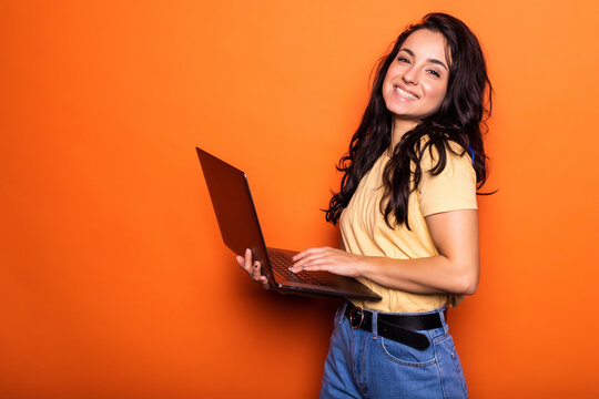 Smiling young blonde woman holding laptop posing isolated on yellow orange background. People lifestyle concept.