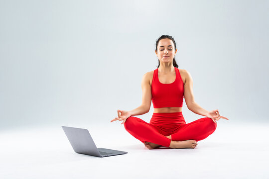 Young pretty woman sitting in yoga pose lotus with laptop isolated on white background