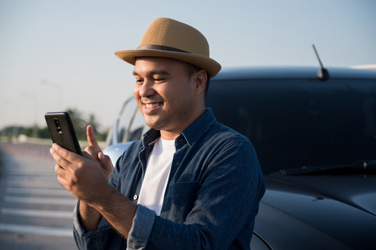 Asian man using smartphone for Off-site car repair service maintenance. Emergency assistance service