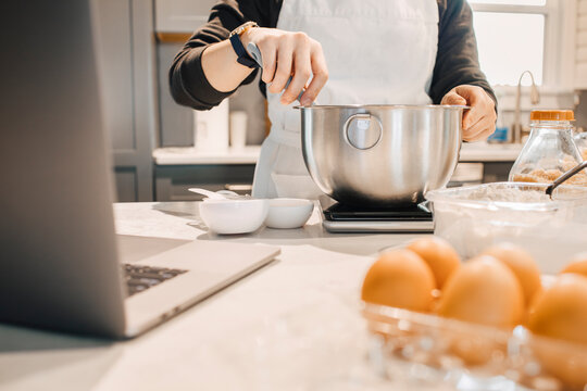 A young chef in a white apron using her bakery equipment, measuring ingredients in a bowl on the scale for a homemade healthy dessert. Culinary learning online via laptop from home. Depth of field
