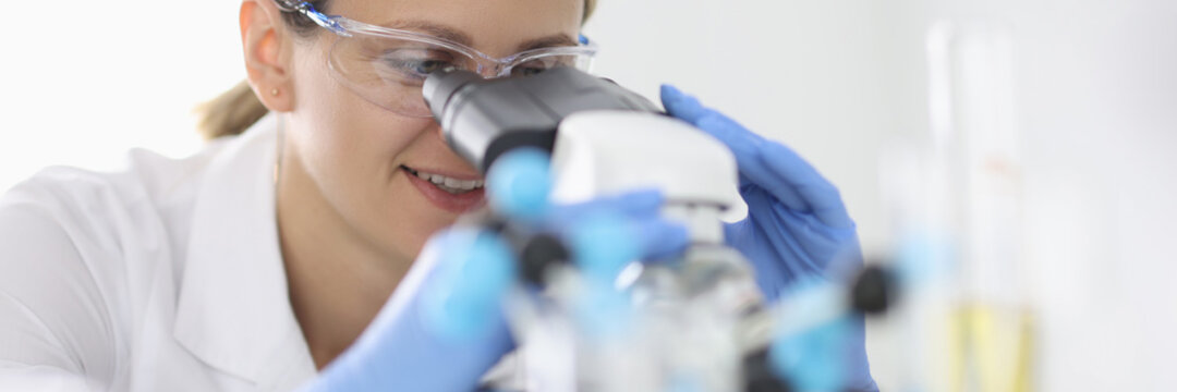Woman in rubber gloves and protective chemical glasses looks through microscope in laboratory portrait. Conducting clinical diagnostic analyzes concept.