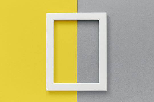 White frame on yellow and gray background. Creative Flat lay Top view Mockup Copy space for text. Trendy colors 2021.