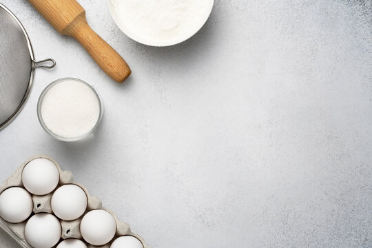 Flat lay with baking ingredients for pastry. Wheat flour, sugar, sieve, rolling pin and white eggs on the grey background. Top view, copy space.