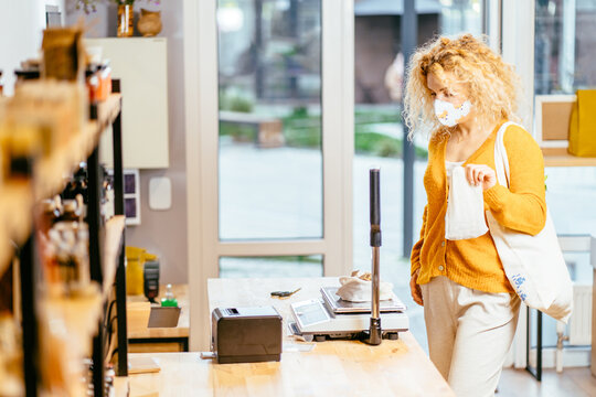Blond curly girl in protective face mask weighing dry goods in plastic free grocery store. Shopping. Eco friendly woman weighting bio food in zero waste shop store or supermarket during virus pandemic