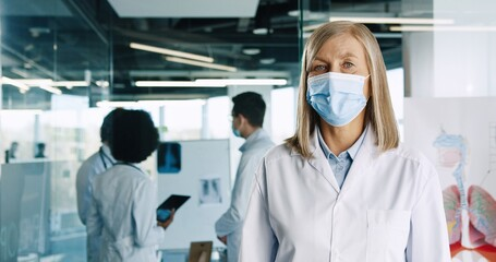 Close up portrait of senior Caucasian female doctor wearing medical mask and white coat standing in...