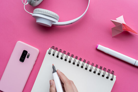 High angle shot of a cellphone, headphones, and writing tools on a pink surface