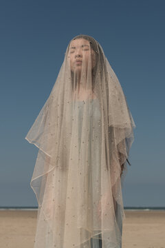 Girl on beach covered by thins white fabric like a virgin mary statue under a blue sky