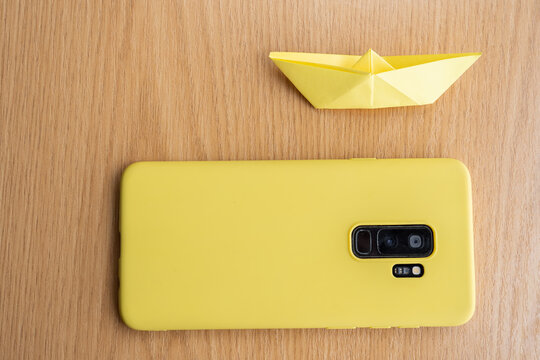 High angle shot of a yellow cellphone and a paper boat on a wooden surface