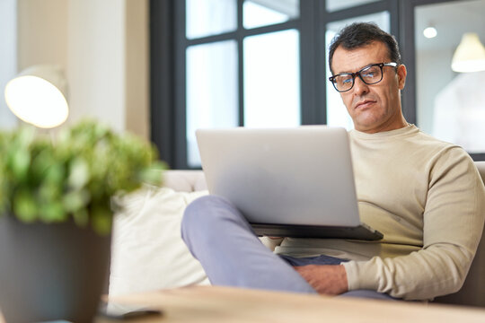 Freelance worker. Portrait of latin middle aged business man with eyeglasses working at home on some project, sitting on a sofa with his laptop