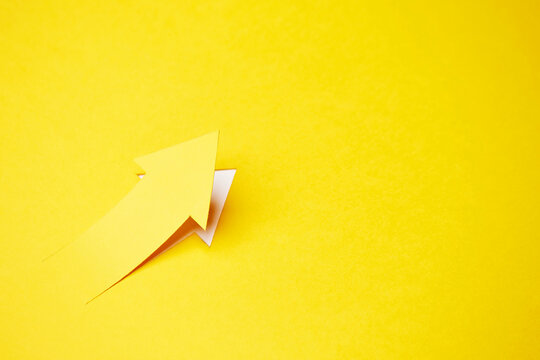 Right-up arrow cutted from solid sheet of yellow paper and curved up of one side with white paper underlay showing growth of stock market or up direction