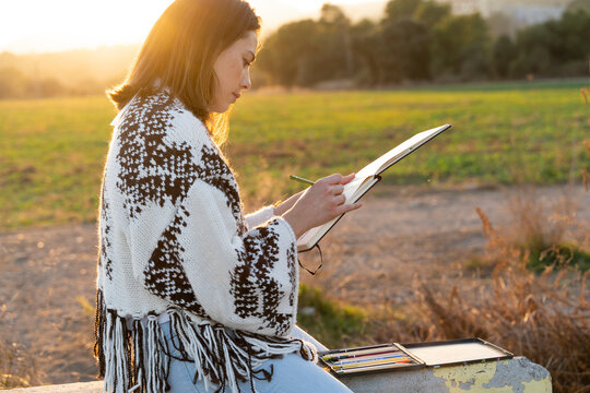 Young woman drawing in book during sunset