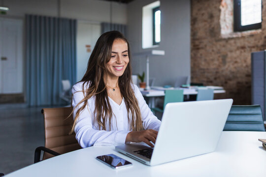 Cheerful businesswoman using laptop at desk in office