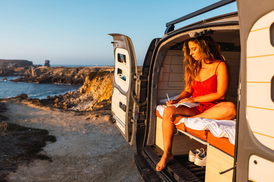 Woman writing in book while sitting in camper van against at beach