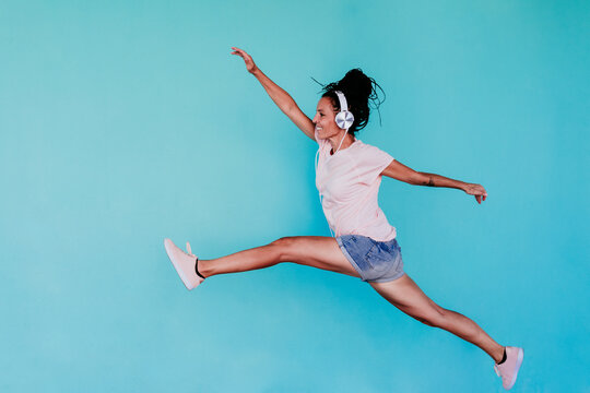 Excited beautiful woman listening music through headphones while jumping against turquoise background