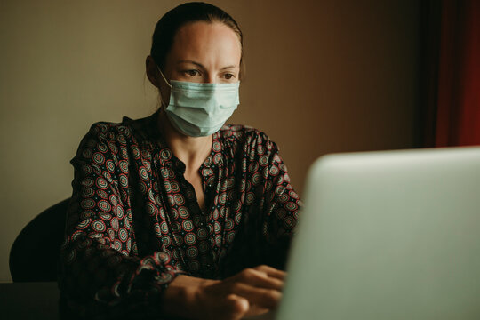 Female entrepreneur wearing protective face mask working on laptop in office during covid-19