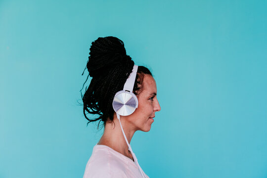 Beautiful woman listening music through headphones against turquoise background