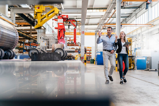Businessman and female colleague pointing while holding digital tablet at factory