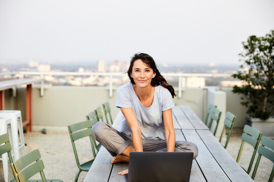 Smiling mature woman with cross legged using laptop while sitting on building terrace