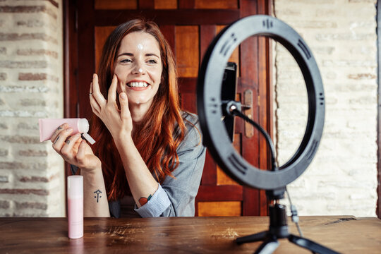 Smiling woman applying cream while filming make up tutorial on mobile phone at home