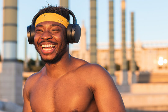 Shirtless man wearing headphones laughing while standing at park