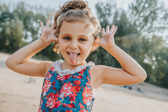 Cute little girl sticking out tongue while standing at beach