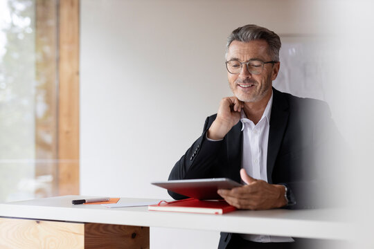 Smiling businessman with hand on chin using digital tablet at home