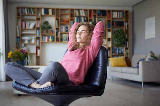 Mid adult woman with hands behind head relaxing on chair at home